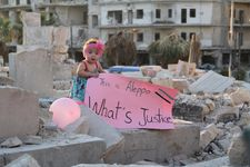 "Sama pictured in September 2016, in the bombarded east of the city with a placard in response to US presidential candidate Gary Johnson's infamous gaffe ""What's Aleppo?"""