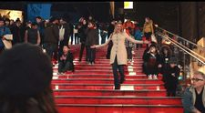 Brooke (Greta Gerwig)descends the red steps over the TKTS booth: