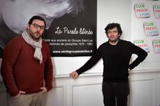 "Denis Ménochet and Éric Caravaca in front of a La Parole Libérée poster: ""I discovered François was very important, he created the association …"""