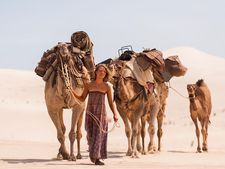Mia Wasikowska as Robyn Davidson in the company of three adult camels and a calf named Goliath.