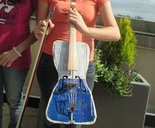 "Ada's violin, built by Colá Gomez: ""This is the cover of a paint tin can. The back is the underside of a baking tin ..."""