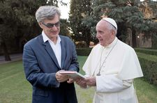 "Pope Francis hands Wim Wenders a copy of his book: ""It's really the Pope's humanity and the way he can bring this into words what is troubling our times."""