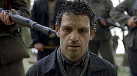 In the horror of Auschwitz, a prisoner (Géza Röhrig) forced to burn the corpses of his own people, tries to save a body he thinks is his son's from the flames in Son Of Saul.